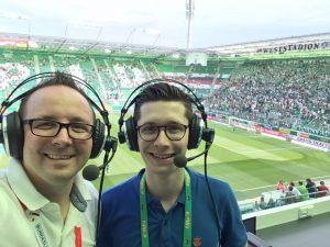 Wolfgang Slavik und Sebastian Aster im Wiener Allianz Stadion beim Bundesliga-Eröffnungsspiel SK RAPID WIEN gegen SV MATTERSBURG. Sie tragen Kopfhörer und stehen vor der Rapid-Fantribüne